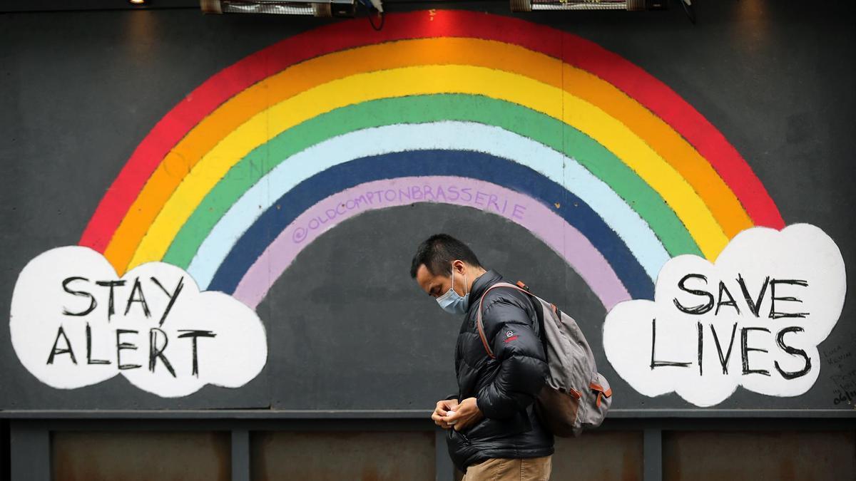 Un hombre con mascarilla pasa por delante de un mural dedicado a la pandemia en Londres.