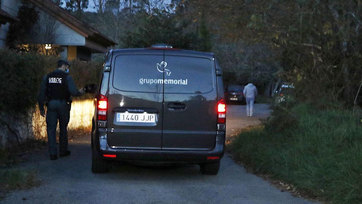 Un furgón fúnebre llega al domicilio del matrimonio, vigilado por un guardia civil.  | // ALBA VILLAR