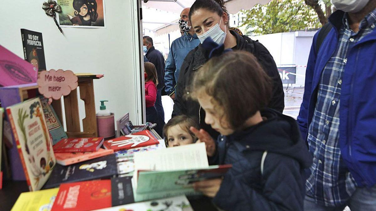 La pequeña Carmen Valdés, ayer, abriendo en el paseo de Begoña un libro junto a su hermana pequeña, María, con sus padres, Sofía Morán y David Valdés, detrás.