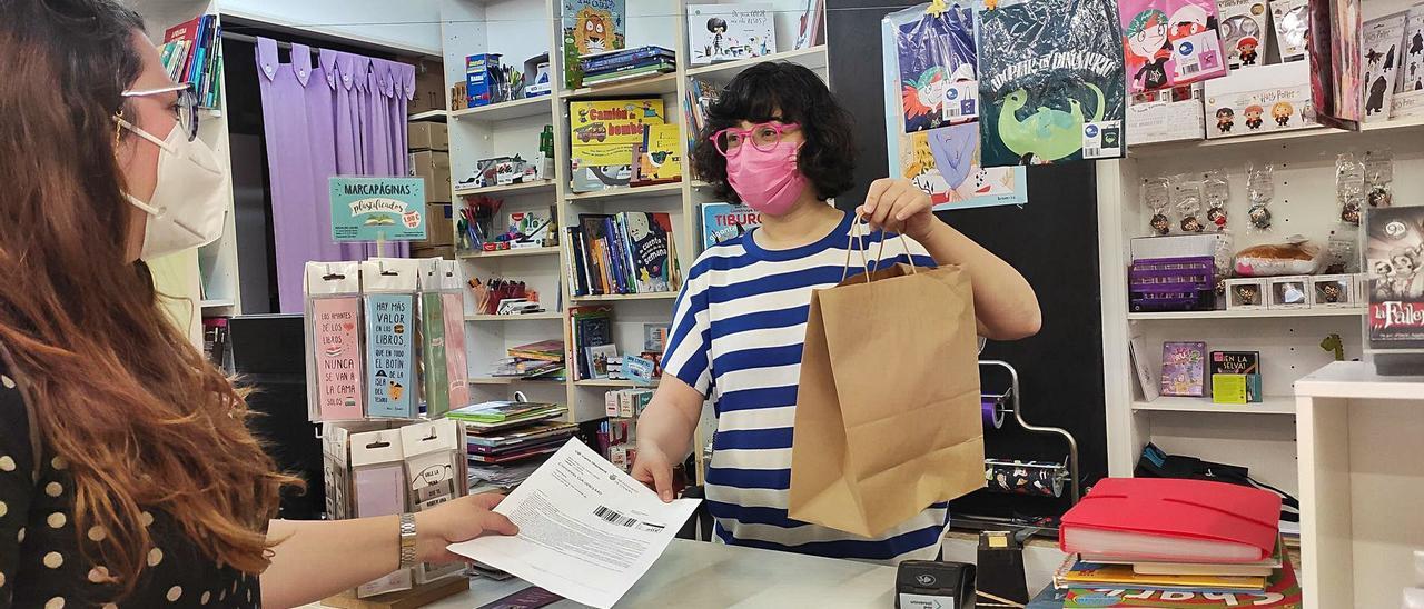 Una clienta, en una tienda de Gandia haciendo uso del cheque-consumo, el pasado mes de mayo. | J. C
