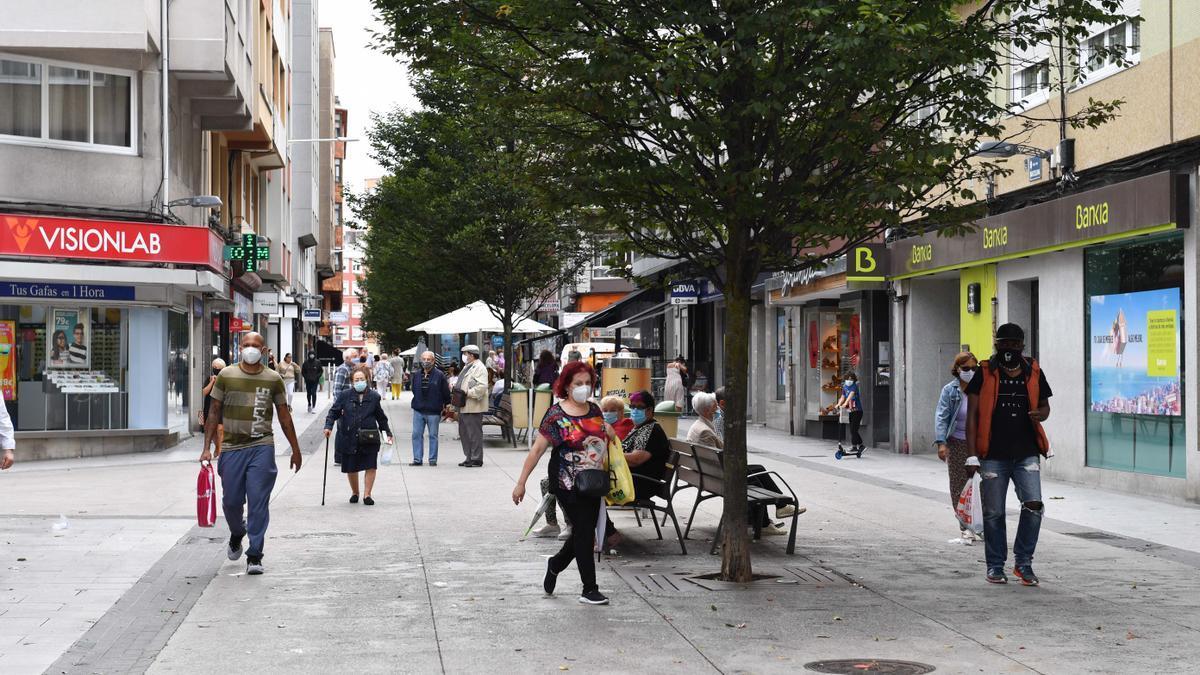Vecinos pasean por la calle Barcelona, en el Agra do Orzán.