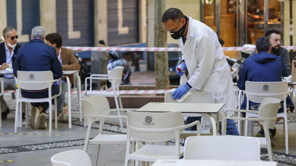 Un hombre limpia las mesas de una terraza en Andalucía