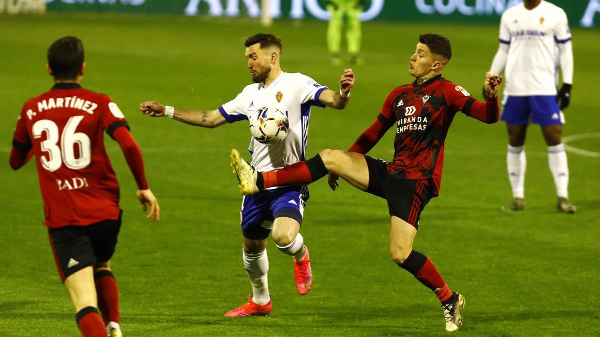 Cristo González intenta arrebatar el balón a Peybernes en el partido del Zaragoza ante el Mirandés.