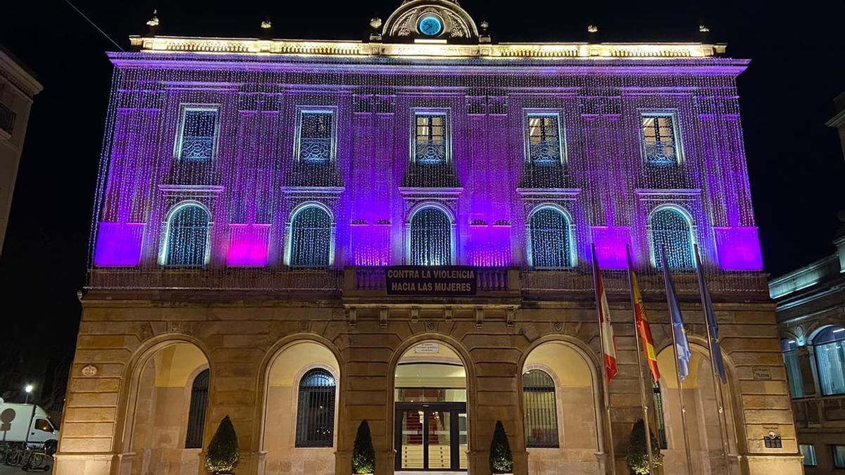 Fachada del Ayuntamiento de Gijón, iluminada de morado