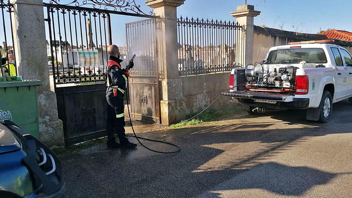 Tareas de desinfección con máquina pulverizadora en el acceso a un cementerio de Lalín.
