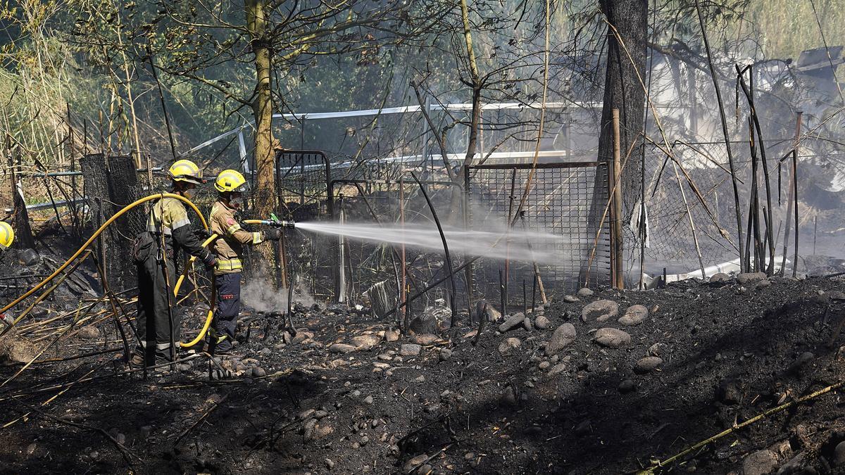 Els Bombers treballen en l'incendi del Pla dels Socs, prop de la barraca cremada.