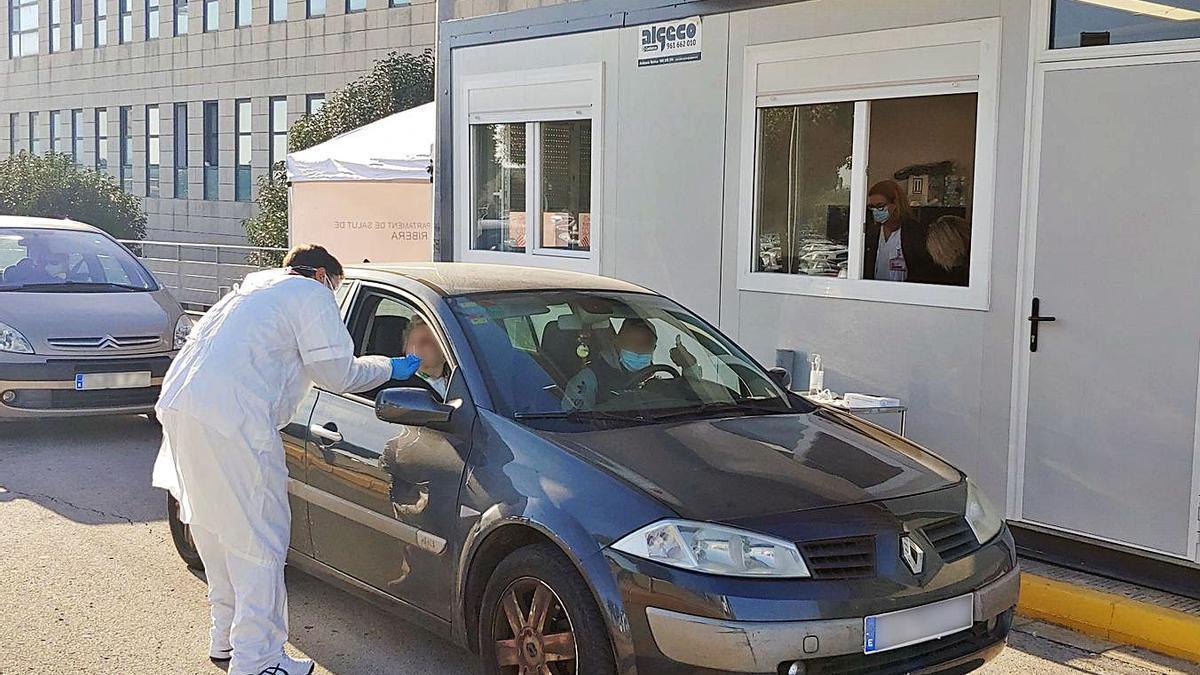 El personal sanitario realiza un test PCR en el puesto habilitado en el exterior del hospital. | LEVANTE-EMV