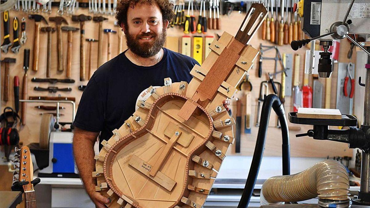 Pablo Sánchez muestra una guitarra que fabrica en su taller.