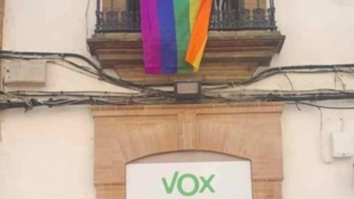 Una vecina coloca una bandera del arcoíris encima de la sede de VOX