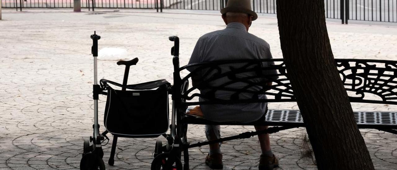 Un hombre mayor, sentado en un banco y con un andador al lado.