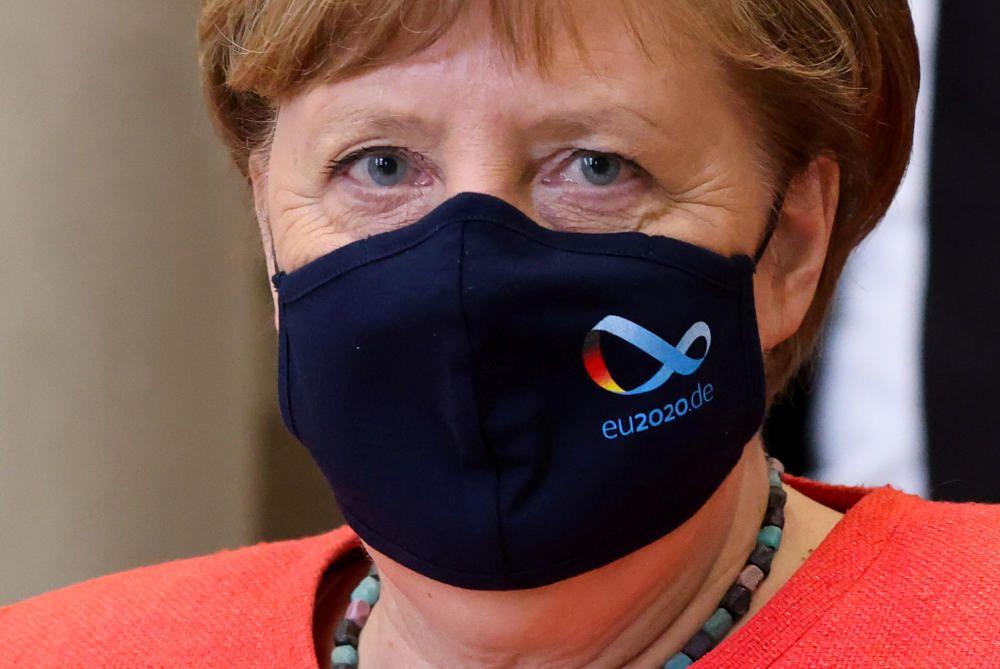 German Chancellor Angela Merkel wearing a face ...