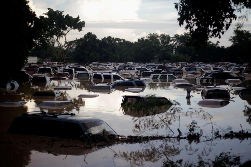 Vehicles are submerged at a plot flooded by the ...