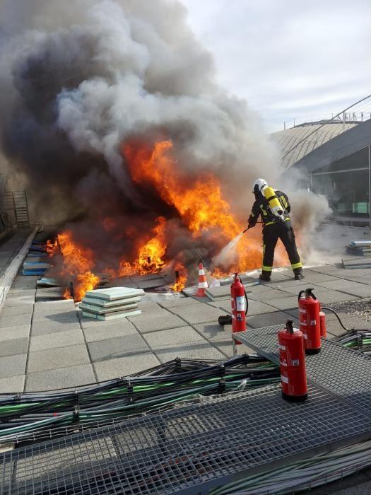 Los bomberos trabajan en la extinción del incendio del aeropuerto de Alicante-Elche