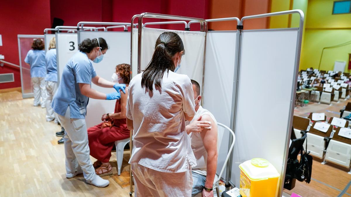 Dos personas reciben la primera dosis de la vacuna de Pfizer en Madrid.