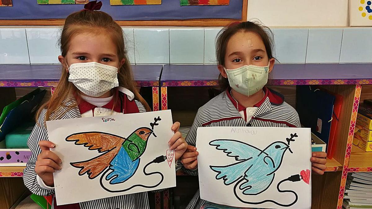 Dos estudiantes de Infantil posan con sus coloridas palomas de la paz.  