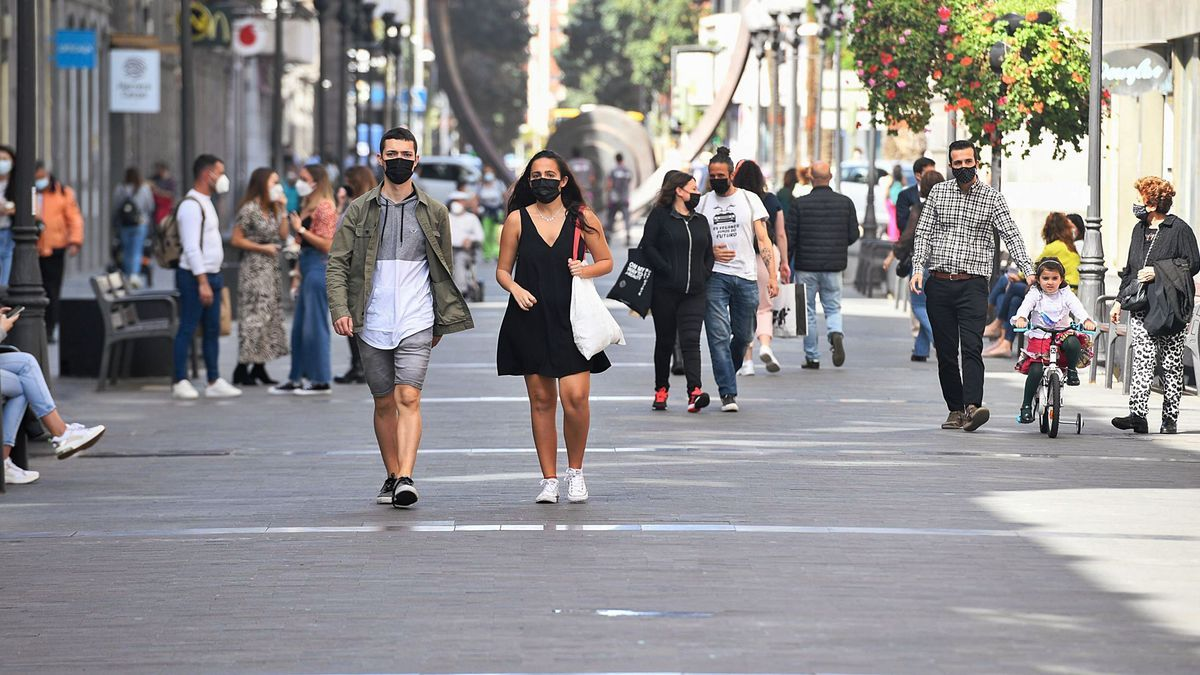 Several people with masks on Triana street.  |  |  JUAN CASTRO