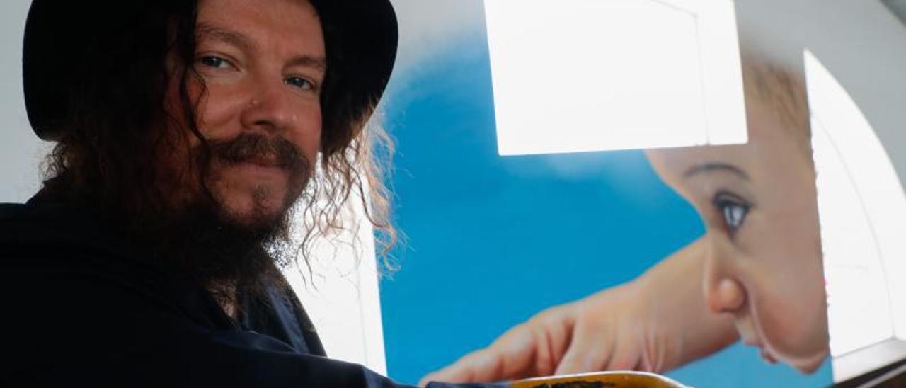 Charlie Granberg subido a la grúa que utilizó para hacer su mural, al fondo, en la Antigua Pescadería.