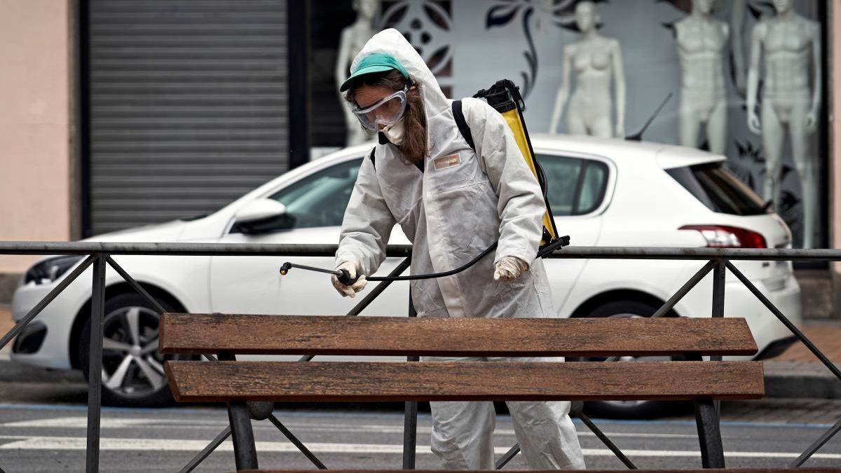 Una operaria desinfectando un banco.
