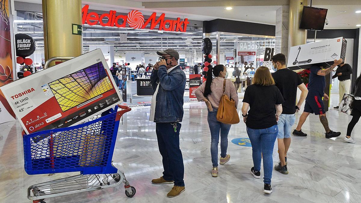 Usuarios de un centro comercial de la capital grancanaria realizan compras durante el 'Black Friday'.