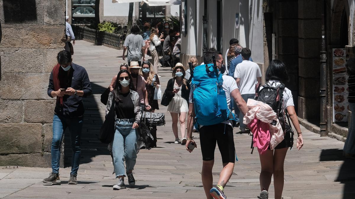 Un grupo de gente pasea por la calle.