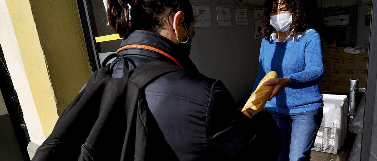 La voluntaria Luisa Torres entrega una barra de pan a uno de los usuarios del centro. | Ricardo Solís