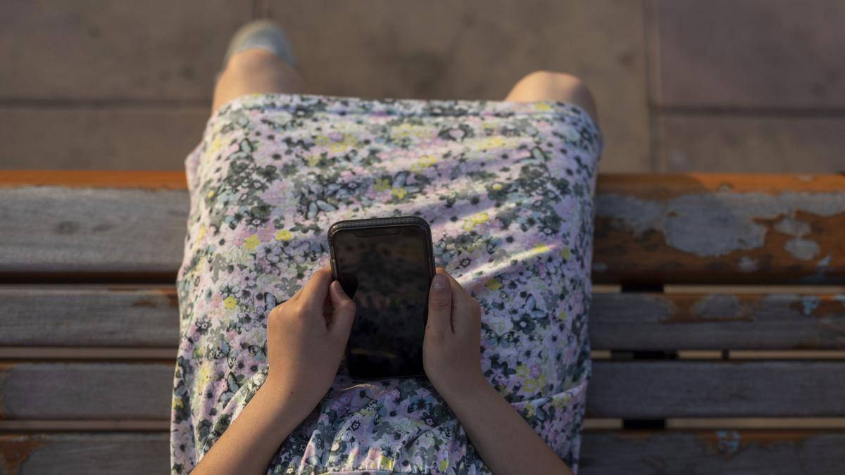 Una joven usa un móvil.