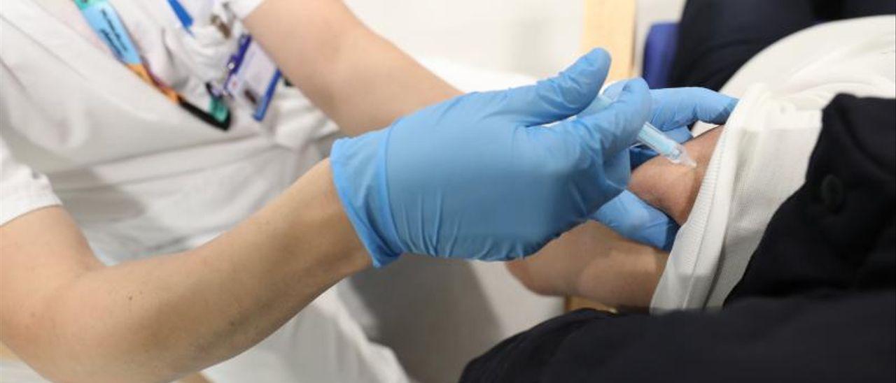 Una enfermera administra una vacuna.