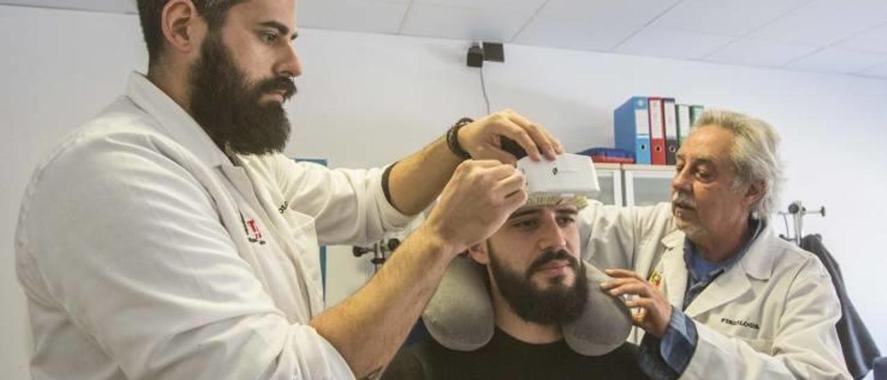 Sergio Molina y Joaquín Ibáñez colocan el dispostivo en otro miembro del equipo de Newmanbrain para realizar una prueba.