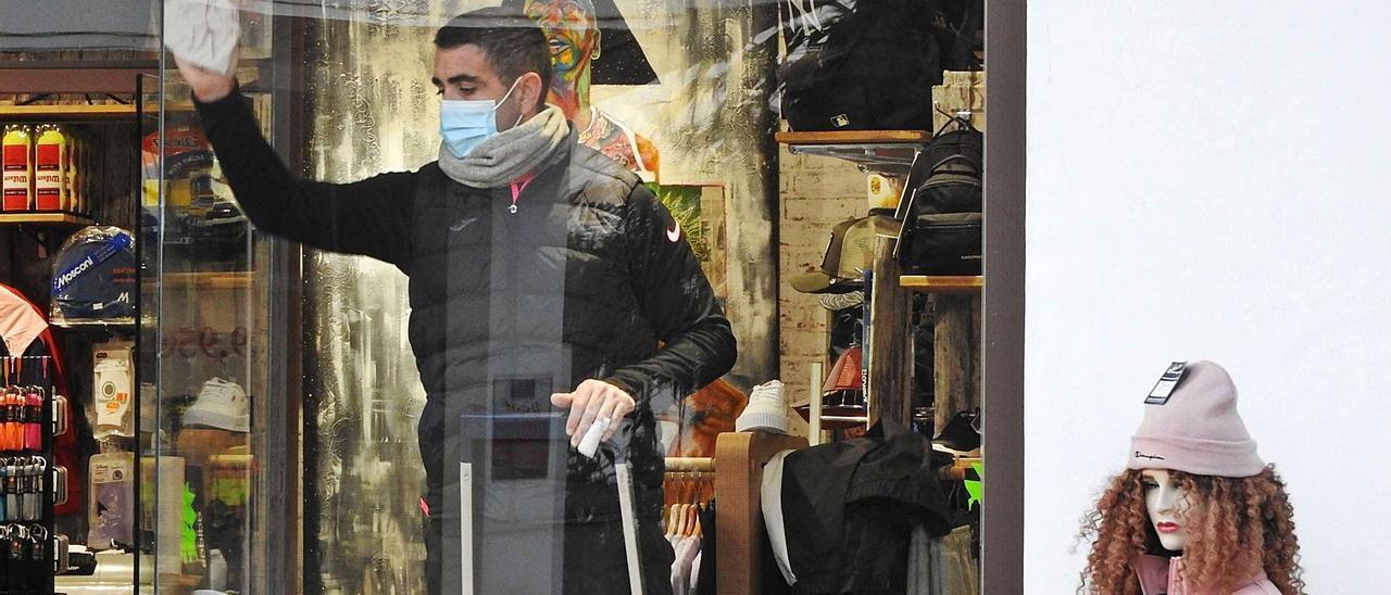 Un comerciante limpia su escaparate en su tienda de Sant Francesc, ayer, en Formentera.