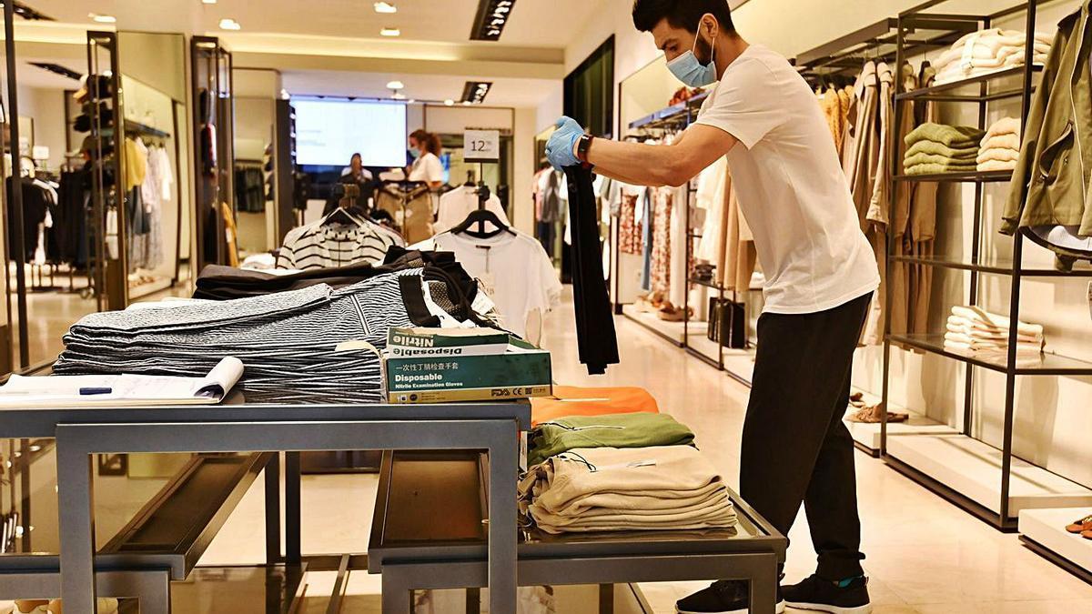 Un dependiente coloca una prenda en una tienda de Zara. |   // GUSTAVO SANTOS