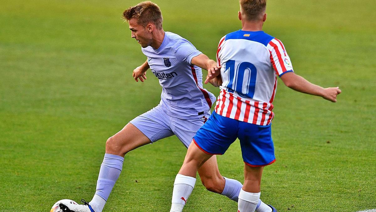 Arnau Comas esquiva l'entrada de Samu Sáiz dissabte durant el partit Barça-Girona a l'estadi Johan Cruyff
