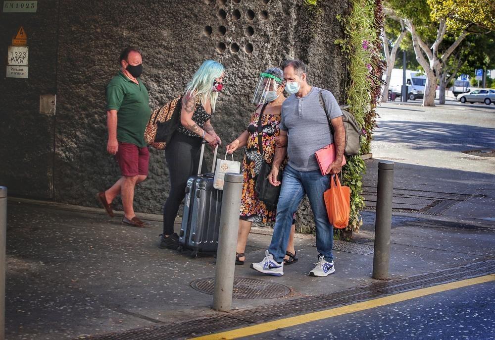 Gente con mascarillas, distancia social, fumadores