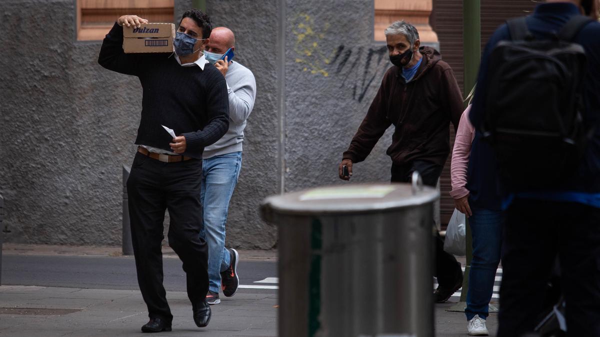 Varios hombres con mascarilla caminan por las calles de Santa Cruz de Tenerife.