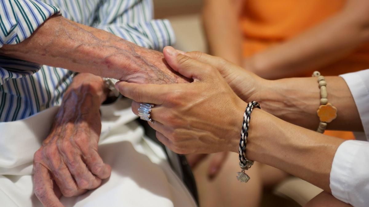 Una cuidadora toma la mano de una persona dependiente.