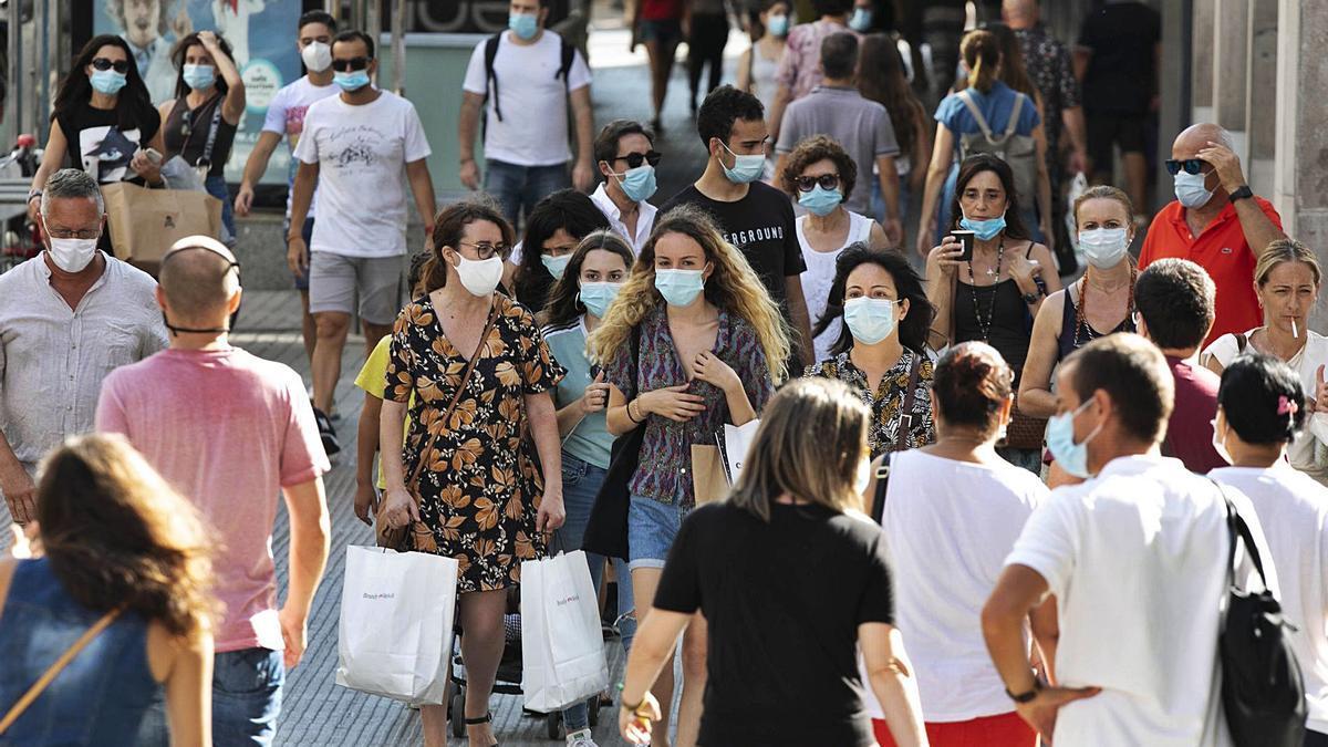 Imagen de archivo de personas en el centro de València con mascarilla.