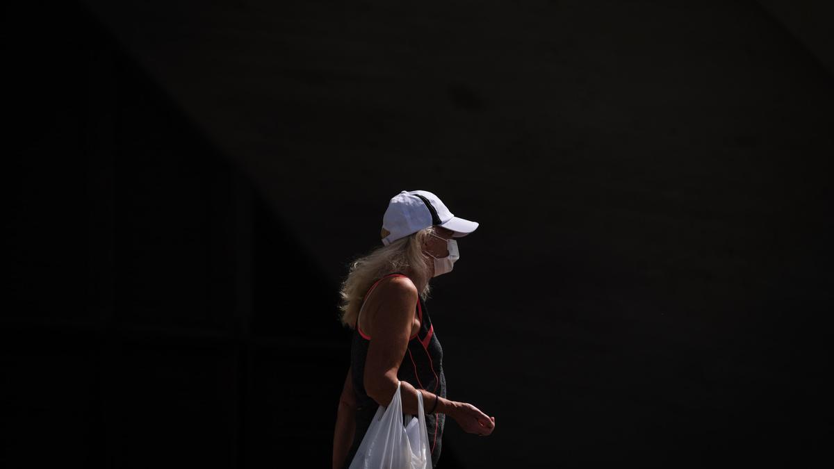 Una mujer con mascarilla camina por Santa Cruz.