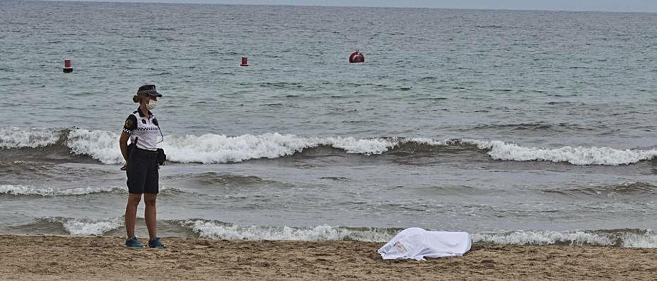 Una policía local junto al cuerpo del bañista fallecido en el Postiguet.  