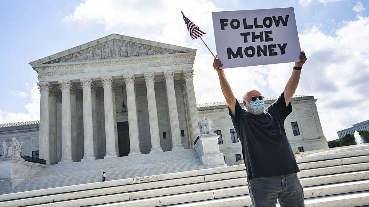 Un manifestante, ayer, ante el Supremo, con un cartel en referencia a las finanzas de Trump.