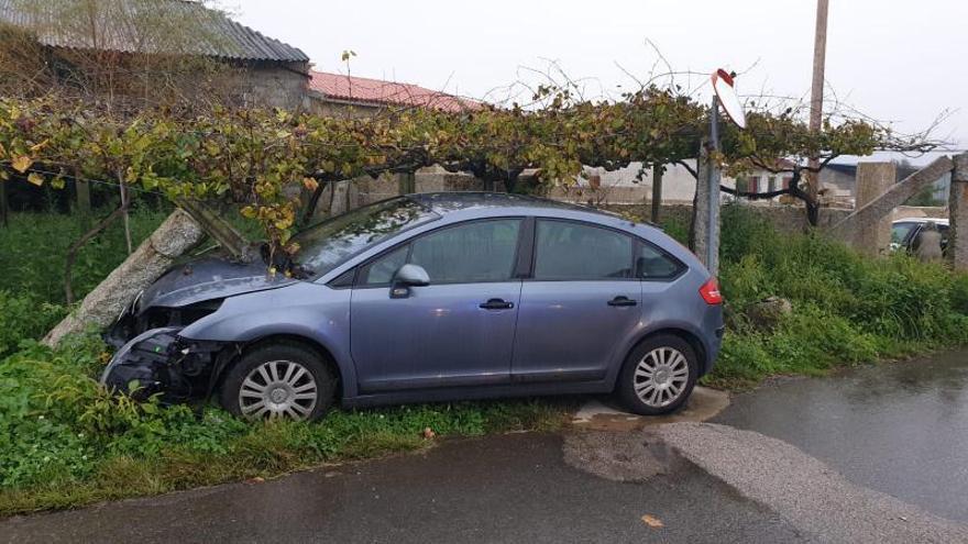 Los dos ocupantes de un coche huyen tras volcar en una rotonda en Pontecesures