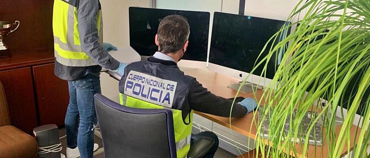 Dos policías con los ordenadores incautados por la estafa con bitcoins. | INFORMACIÓN