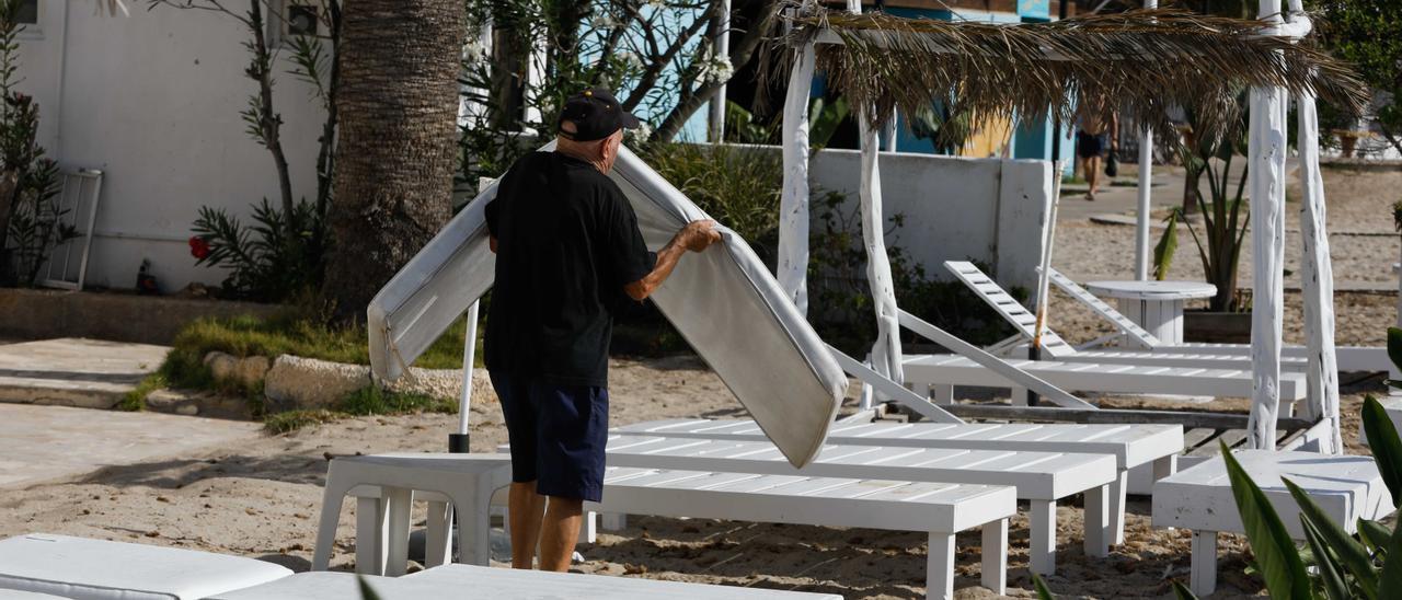 Un hombre prepara las hamacas de la playa de Talamanca.