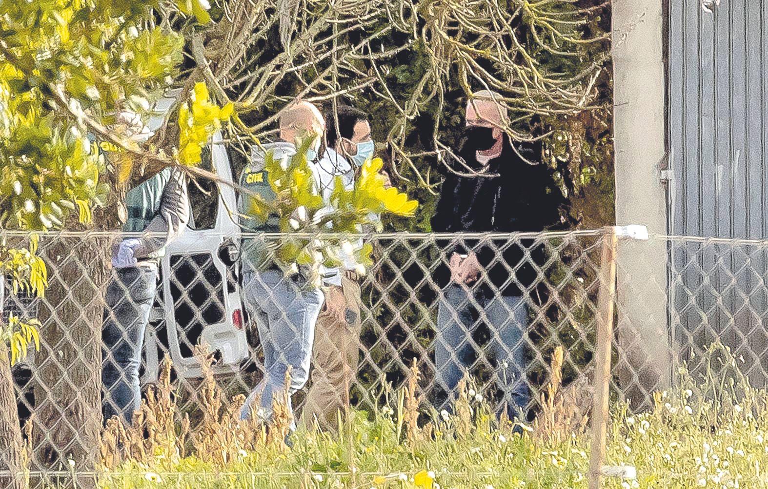 El sospechoso, esposado a la derecha, con los investigadores de la Guardia Civil durante el registro.