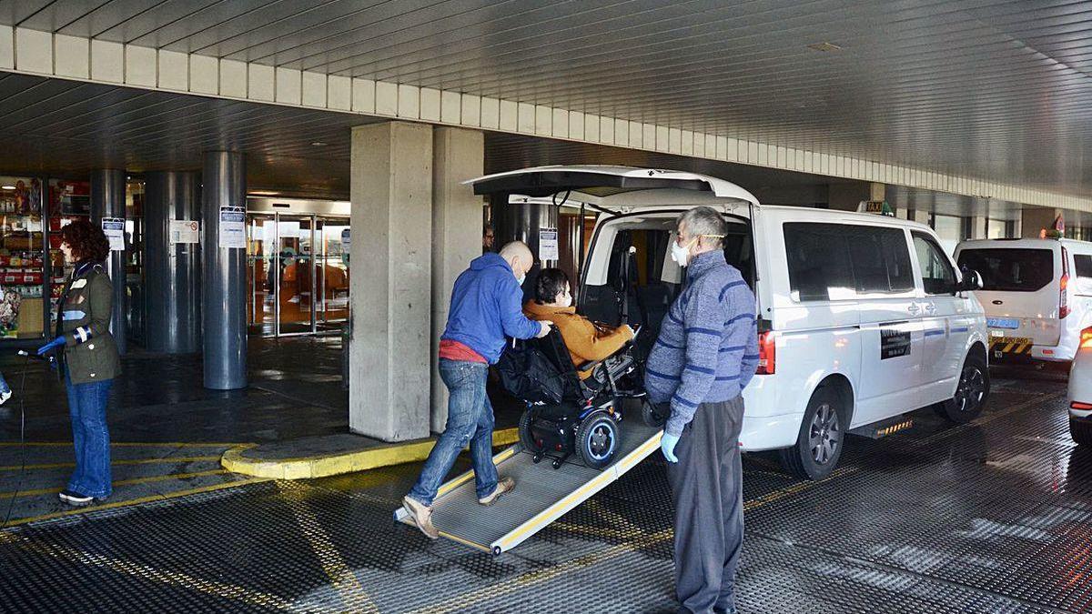Un hombre en silla de ruedas es ayudado para subirse a un taxi.