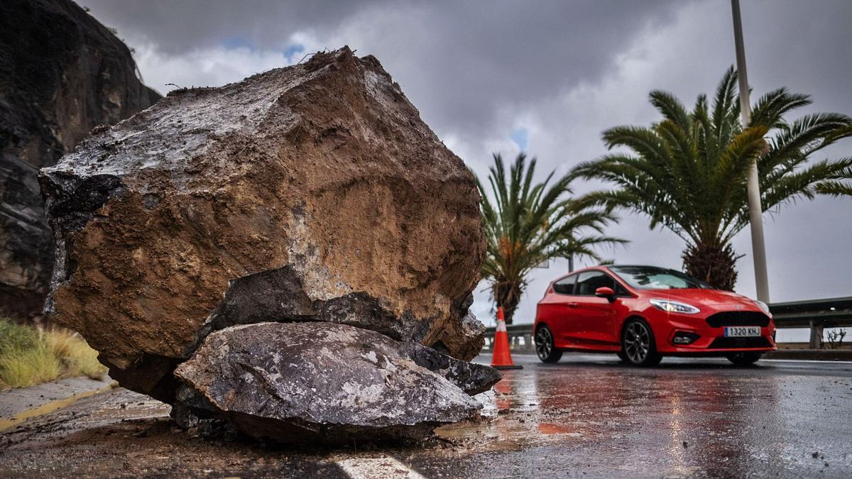 En la fotografía de la izquierda, imagen de la piedra que cayó en la autovía de San Andrés, a cien metros de la salida del pueblo. Arriba, estado de la autopista del Norte en el mediodía de ayer, una jornada pasada por agua que también sorprendió a transeúntes de la capital.   carsten lauritsen/andrés gutiérrez