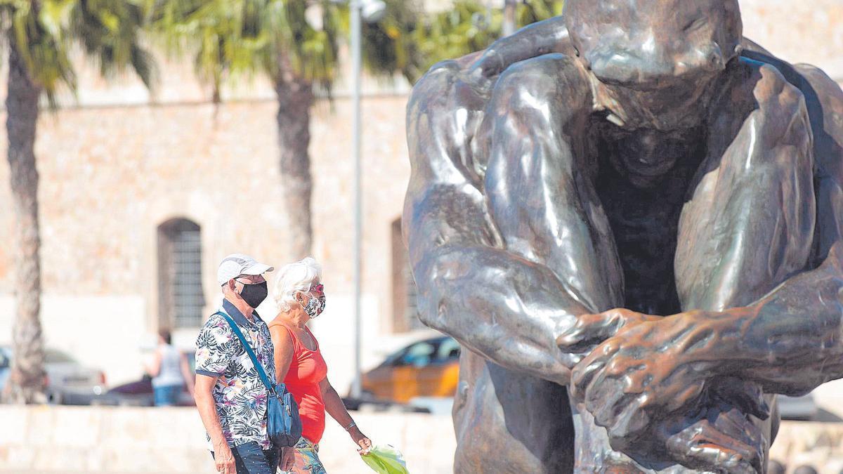 Dos turistas frente a la escultura 'El zulo', en Cartagena.