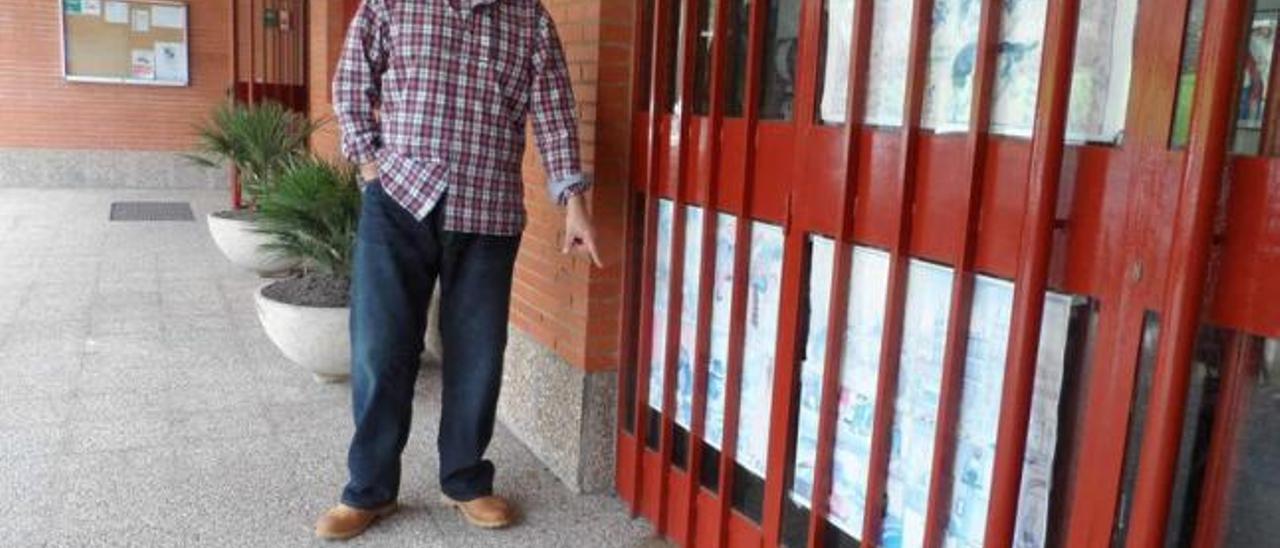 Benigno Expósito, ayer, señalando las marcas que dejaron los vómitos de los gatos en la entrada al colegio.