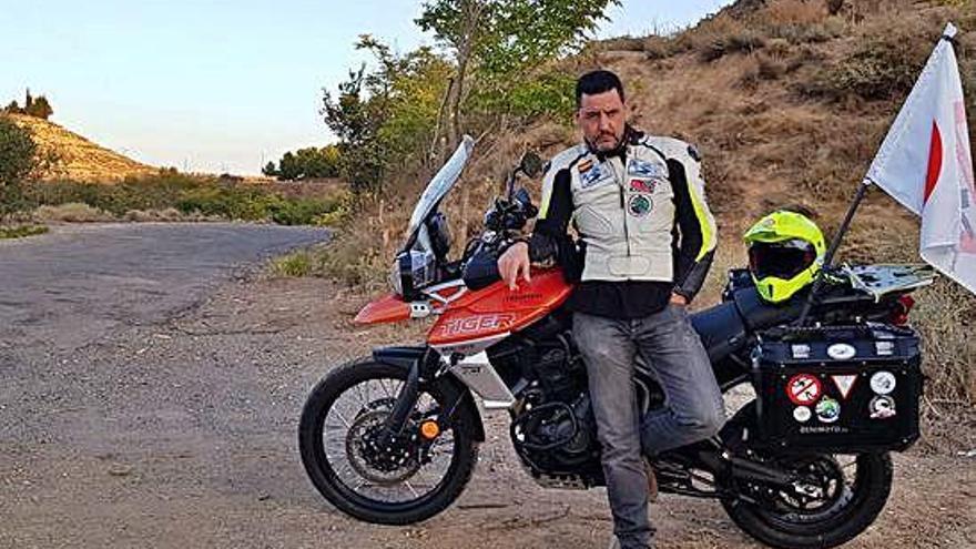 PJuan Carlos Toribio posa con la moto en un carretera en mal estado.