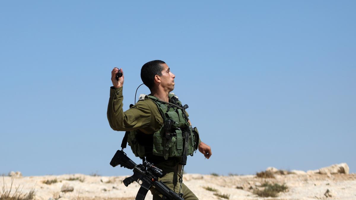 Un Policía israelí lanzando un objeto contra manifestantes palestinos.