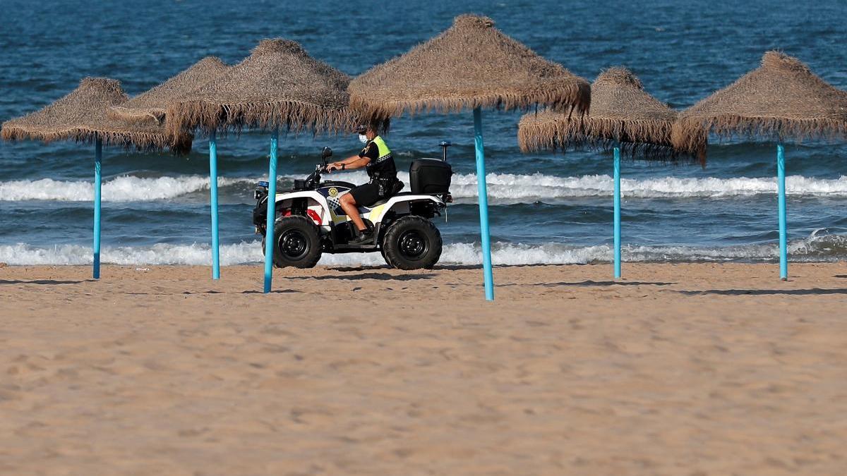 Un agente vigila la playa en València en la noche de San Juan.