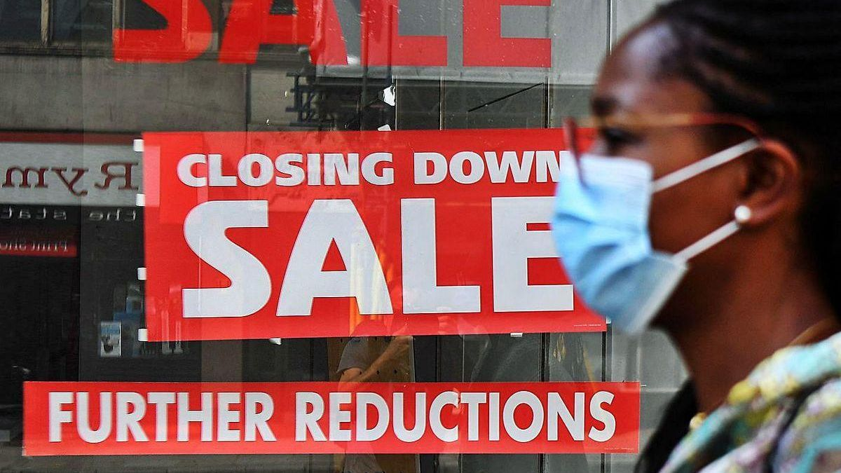Una mujer con mascarilla pasa junto al escaparate de un comercio en liquidación en Londres.